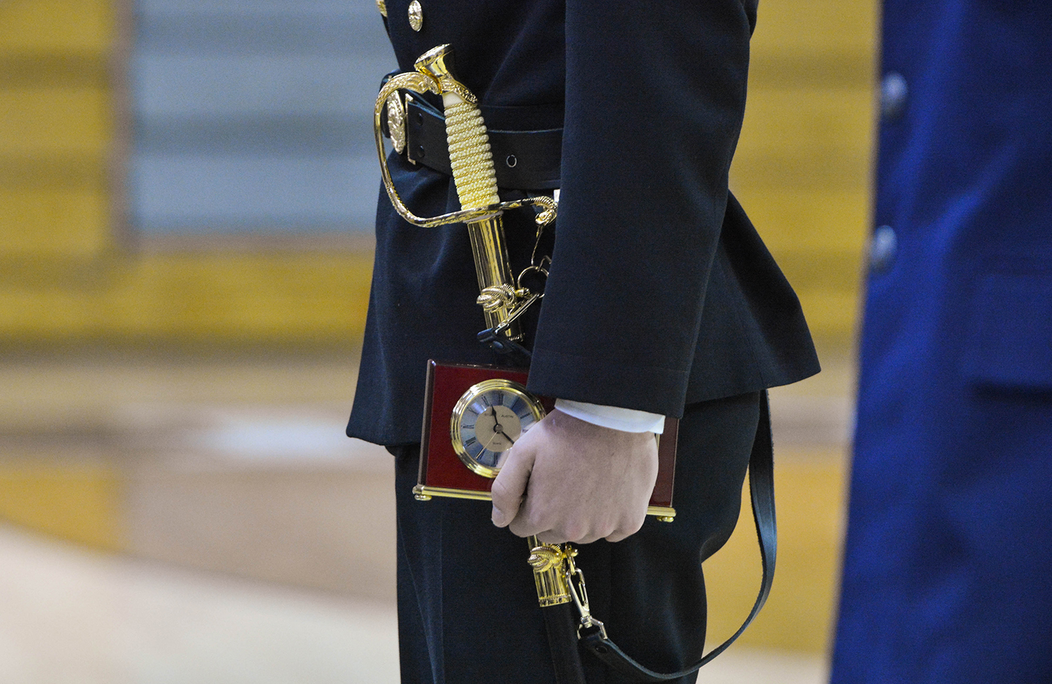 ROTC student holds sheathed weapon and clock.