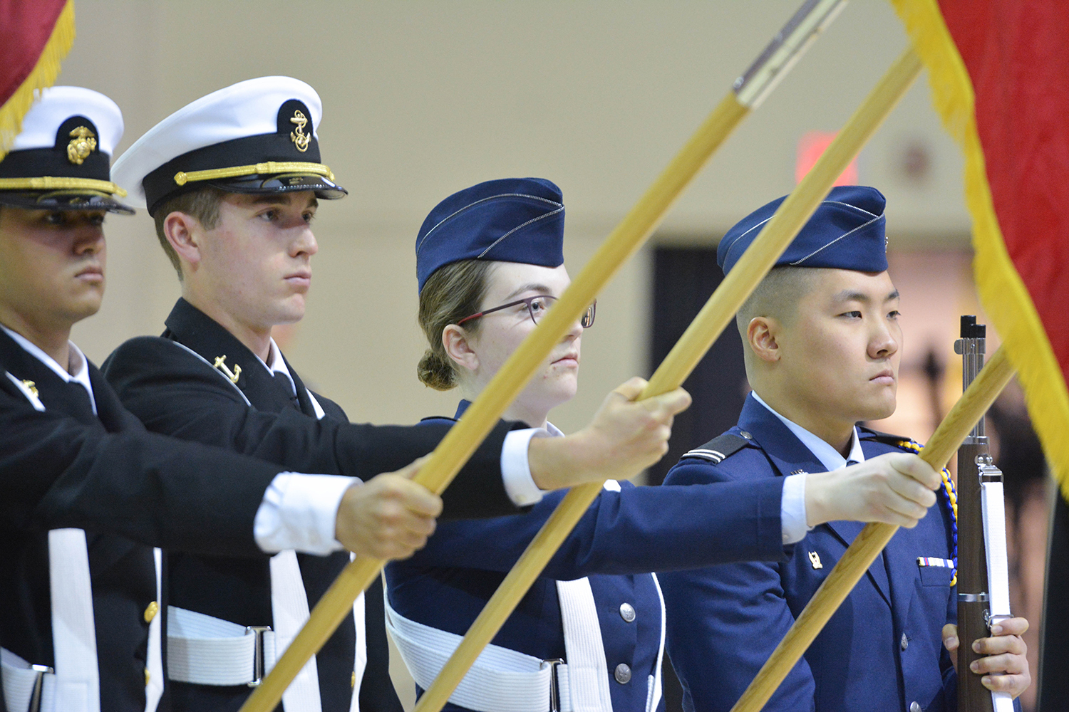 ROTC students hold flags and a firearm